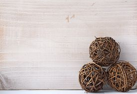 Three Rattan Balls On A Light Background Old Wooden