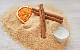 Brown Sugar, Cinnamon Sticks, Candied Orange And A Candle On A Light Wooden Background