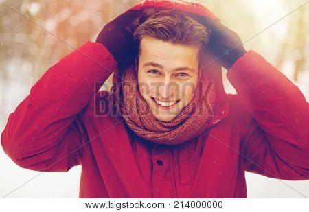 people, christmas, winter and season concept - happy smiling man in jacket and scarf wearing hood outdoors