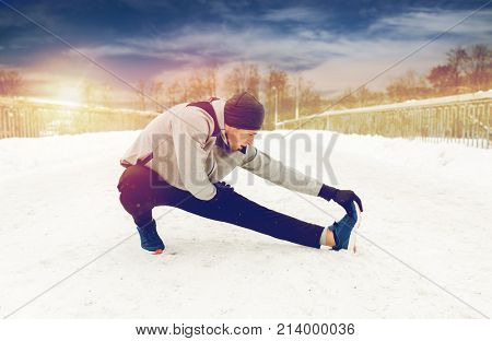 fitness, sport, people, exercising and healthy lifestyle concept - young man stretching leg and warming up on snow covered winter bridge