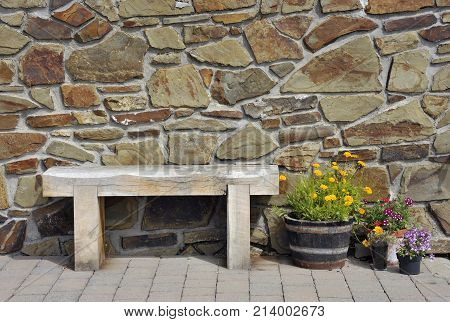 Bench seat flowers and stone wall background in Tenby Wales UK.