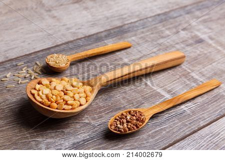 Wooden spoons are different in size with peas, buckwheat and rice lie down horizontally and are directed to the left at an angle