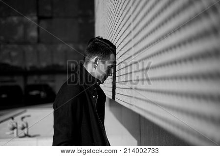 The young man is unhappy in a dead end or depression. Stands leaning his forehead against the wall. Black and white picture