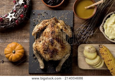 high-angle shot of a roast turkey placed on a rustic wooden table next to some bowls with gravy, mashed potatoes, blueberry jam, some slices of roasted potato or a roasted corn