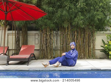 attractive woman in a Muslim swimwear burkini on a pool side in a tropical garden