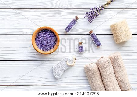 Set for foot spa with lavender. Flowers, spa salt, pumice stone, soap on white wooden background top view.