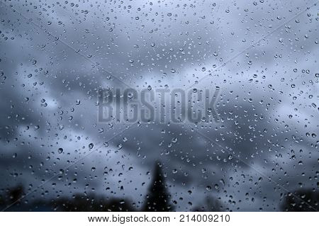Window glass covered with drops falling outside the rain. The view behind the window is blurred, unclear. You see the dark, rainy clouds.