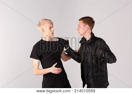 Two young guys fight. The brunette guy is holding the blonde guy by the T-shirt and swinging his fist at him. Isolation.