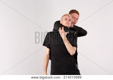 Two young guys are brunette and blond are fighting. A guy with dark hair dominates and does strangulation with the help of hand. Isolation.