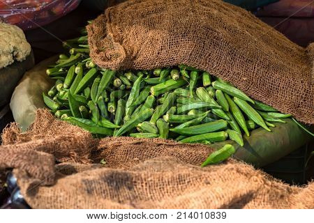 Close up fresh green okra or ladies' fingers lying on sack in market