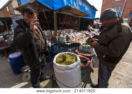 OLGIY, BAYAN-OLGIY, MONGOLIA - SEP 27, 2017: Unknown man in the city market sells loose tobacco. In Bayan-Olgiy province is populated to 88,7% by Kazakhs.