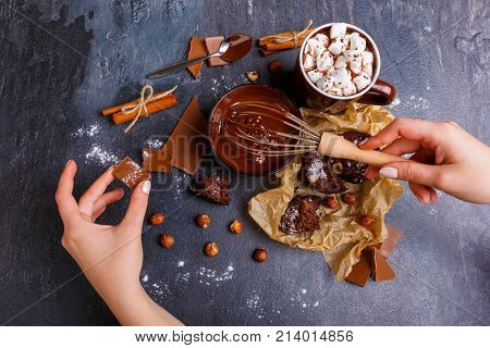 Hand hampered melted chocolate with hazelnuts, in the other hand a piece of chocolate. A cup of marshmallow in chocolate, a cake on a wrapper, hazelnuts, cinnamon sticks with sugar powder