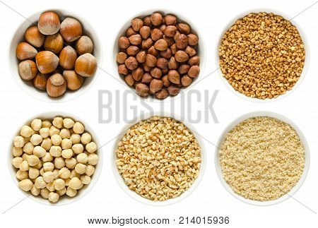 Hazelnuts in white bowls. Whole nuts, shelled, blanched and roughly chopped. Ground hazelnuts and hazelnut brittle. Corylus avellana. Macro photo, close up, from above, isolated, on white background.