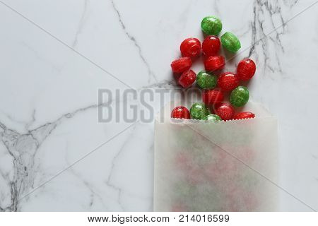Red and green hard candies spill out of bag onto white marble copy space.