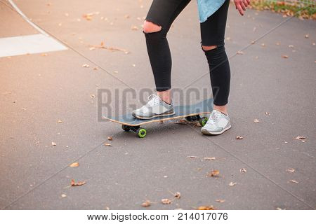 A girl skater in tattered pants kneeling stands with one foot on a skateboard in a skate park