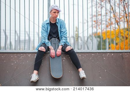 A young girl in tattered pants sits on top of an overclock with a skate in her hand