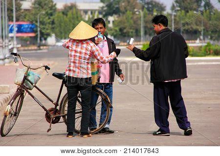 Vientiane, Laos - November 29: Unidentified Men Buy Ice Cream From Street Seller On November 29, 201