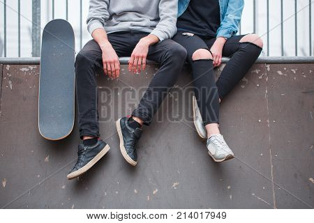 The girl and the guy are sitting on the counter by dangling their feet down next to the skateboard in the skate park. Front view