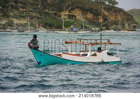 RINCA INDONESIA-MARCH 15: Unidentified men sit in traditional boat in Komodo National Park on March 152012 in Nusa Tenggara Indonesia. Most of the people in Komodo National Park make their living out of fishing