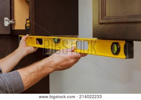 Rear View Of Serviceman Fixing Cabinet Kitchen