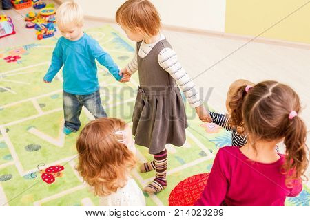 Group of little children dancing holding hands and enthusiastically watching the boy, who laughs with joy