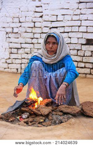 Agra, India-january 30: Unidentified Woman Makes Fire Using Dry Cow Dung In Taj Ganj Neighborhood On