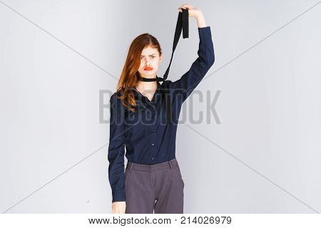 red-haired girl with red lips and in a black shirt tries to strangle herself with a tie and looks into the camera, isolated