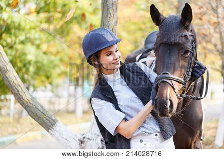 Close-up of a young girl, with a horse standing in the fresh air, in an autumn park, looking at the horse and hugging her horse's face with her hands.