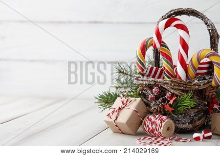Christmas wicker basket with striped candy canes and gifts on white wooden table festive decoration