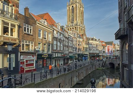 UTRECHT, HOLLAND, JUNE, 14, 2017: Summer view on European old classic buildings houses, city water channel and walking people. European classical architecture buildings houses villas. City church