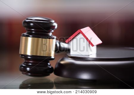 Close-up Of Gavel With Small House Model In Courtroom