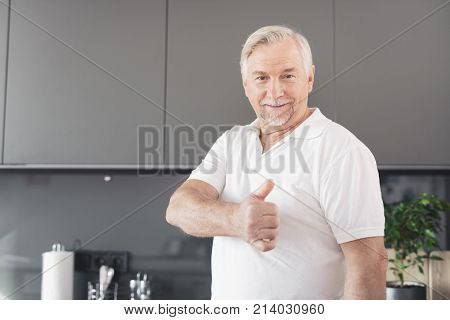 The man is in the kitchen. He shows his thumb up. He has a white T-shirt, a gray beard and hair. A man is in a modern kitchen.