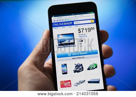 Close-up Of Person's Hand Shopping Online On Mobile Phone Over Blue Background