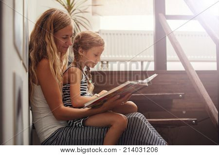 Mother with girl reading book. Female with child at home