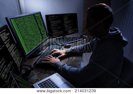 Side View Of Hacker Stealing Information From Multiple Computers On Wooden Desk