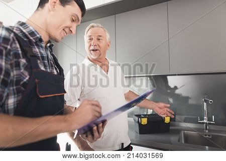 Two men of plumbers are standing in the kitchen. An elderly man inspects the place of repair work. The second man makes notes on his form. Next to them is a black tool box.