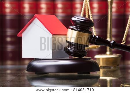 Close-up Of Gavel And House Model On Sounding Block