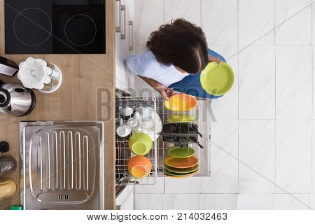 High Angle View Of Young Woman Arranging Plates In Dishwasher At Home