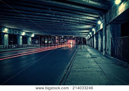 Fire trucks, ambulance, police and traffic in a dark Chicago tunnel viaduct street at night.