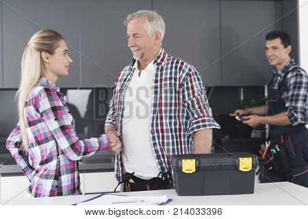 The woman shakes her hand and thanks the plumbers for the repairs. A young plumber examines the kitchen sink. A black toolbox is next to it.