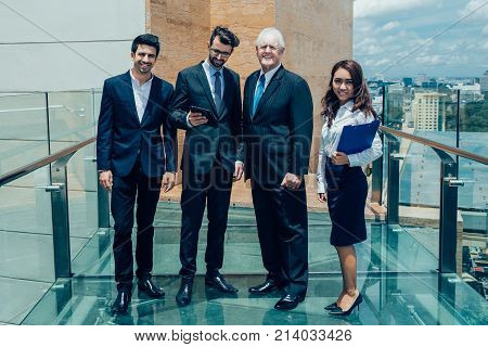 Group of four successful business people standing on rooftop of modern office building and smiling. Team concept