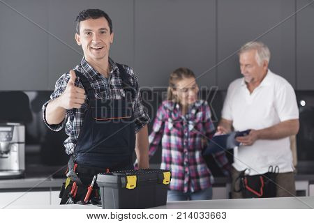 The plumber is posing in the kitchen. He shows his thumb up and smiles. Behind him is a client and communicates with the second plumber. A black toolbox is next to it.