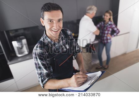 The plumber is posing in the kitchen. He fills out the form and smiles. Behind him is a client and communicates with the second plumber. A black toolbox is next to it.