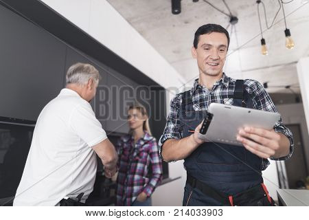 The plumber is posing in the kitchen. He looks at the tablet and smiles. Behind him is a client and communicates with the second plumber. A black toolbox is next to it.