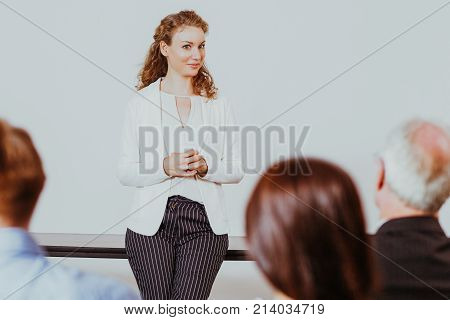 Smiling young attractive businesswoman leaning on table and looking at audience with three people seen. Rear view of audience.