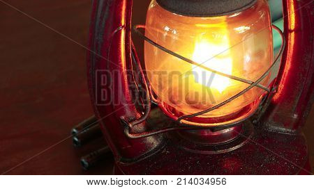 Vintage oil lamp antique stands on the table in the dark. Oil filled lantern in dark room.