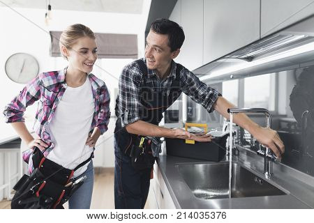 A man and a woman plumber repair a kitchen faucet from the client at home. The man checks the work of the mixer, the woman is busy at work. Next to them is a black tool box.