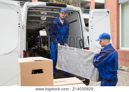 Two Young Male Worker In Blue Uniform Unloading Furniture From Truck