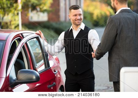 Smiling Young Male Valet And Businessperson Standing Near Red Car