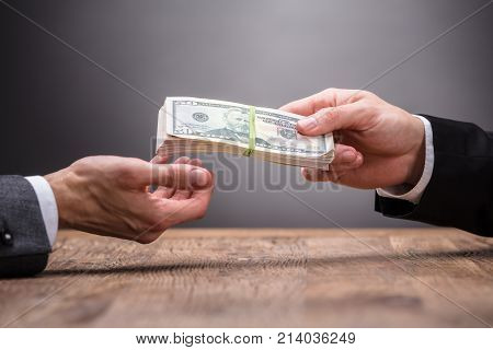 Close-up Of A Person Giving Bribe To Businessperson At Workplace